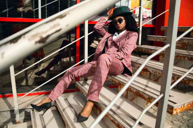 woman wearing pink suit jacket and pants sitting on staircase