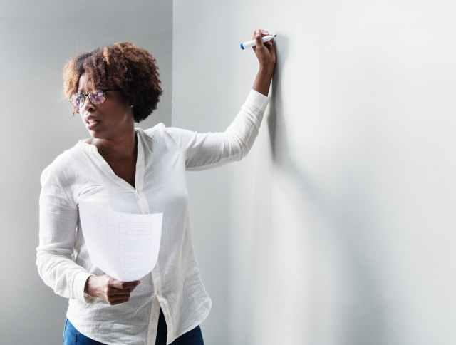 woman writing in white board